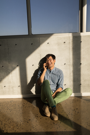 Front view of young Asian male executive talking on mobile phone sitting on the floor in modern office.
