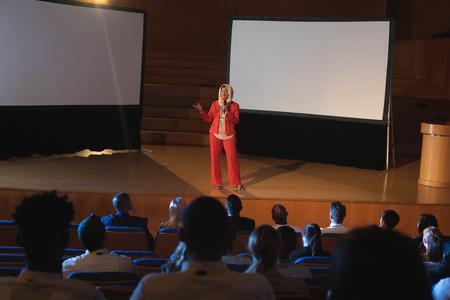 Vorderansicht einer glücklichen gemischten Geschäftsfrau, die im Auditorium steht und eine Präsentation hält, während sie das Mikrofon in der Hand hält