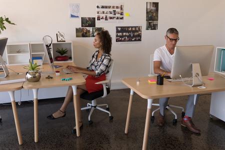 Zijaanzicht van gemengd ras en blanke zakenpartners die aan hun bureau in een modern kantoor werken. Ze concentreren zich en plannen.