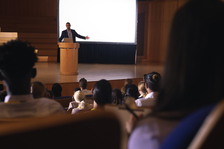 Front view of mixed race businessman giving presentation on white projector in front of the audience Фото со стока