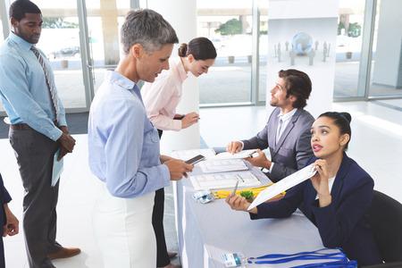 Vista lateral de diversos empresarios que se registran en la mesa de registro de conferencias en el vestíbulo de la oficina Foto de archivo
