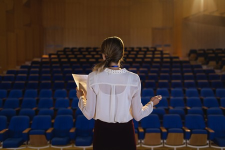 Rear view of beautiful Caucasian businesswoman practicing and learning script while standing in the auditorium