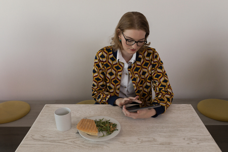 Front view of young beautiful Caucasian female executive using digital tablet in canteen at modern office Stok Fotoğraf - 122296476