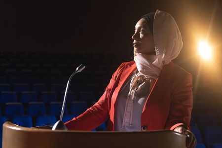 Front view of beautiful mixed race businesswoman looking and thinking while standing on stage in auditorium Stok Fotoğraf
