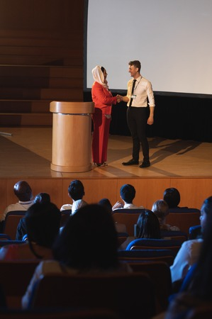 Front view of mixed race business colleague standing and discussing with each other in front of the audience in auditorium while shaking hand