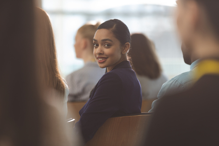 Portrait of happy young mixed race businesswoman looking at camera during seminar in office building