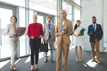 Portrait of mixed race business people looking at camera while standing in modern office building