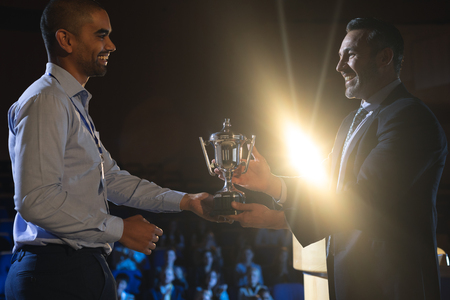 Side view of Caucasian businessman giving trophy to mixed race business male executive on stage in auditorium Stok Fotoğraf - 122296806