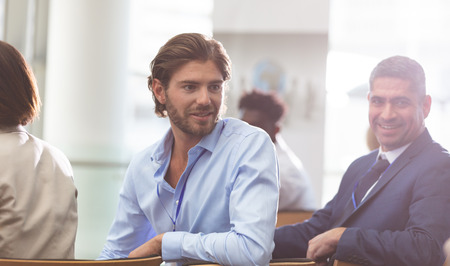 Front view of Caucasian businessman attending a business seminar while he speaks with coworkers in office building