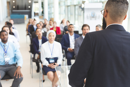 Rear view of  mixed race male speaker speaks to diverse business people  in a business seminar in a conference room Stok Fotoğraf