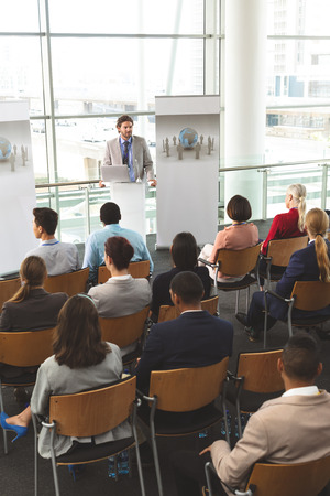 High angle view of Caucasian male speaker with laptop having a presentation in front of business people sitting at business seminar in office building Stock Photo - 122295400