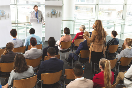 High angle view of Caucasian businesswoman interacting with Caucasian businessman speaking in front of business people sitting at business seminar in modern office building