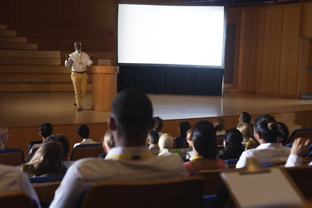 High view of matured African-American businessman standing and giving presentation in auditorium Standard-Bild - 122295413