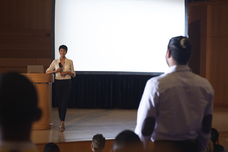 Front view of beautiful Asian businesswoman discussing while woman from the audience standing and asking query in the auditorium Stok Fotoğraf - 122297219