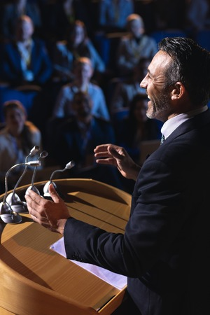 Side view of Caucasian businessman standing and giving presentation in the auditorium Stok Fotoğraf - 122297220