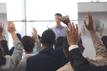 Rear view of diverse business people raising hands in a business seminar in office building Stok Fotoğraf - 122297224