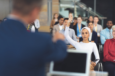 Front view of mixed race businesswoman raising hand at a business seminar in modern office building