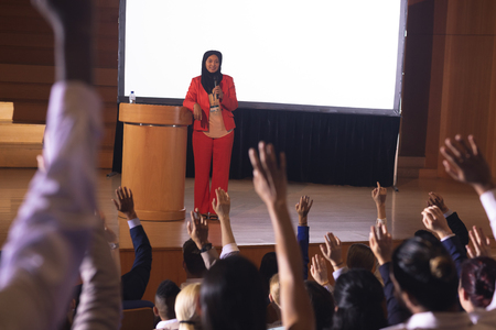 Front view mixed race businesswoman standing around the podium in the auditorium while audience raising hand for asking question