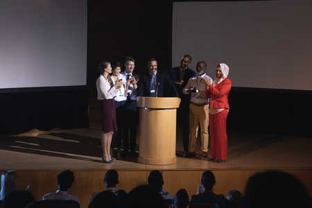 Front view of mixed race business colleagues clapping hand for there colleague  for the success in the auditorium stage in front of the audience Reklamní fotografie