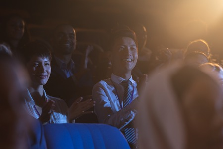 Front view of mixed race business colleagues sitting and watching presentation with audience and clapping hands Reklamní fotografie