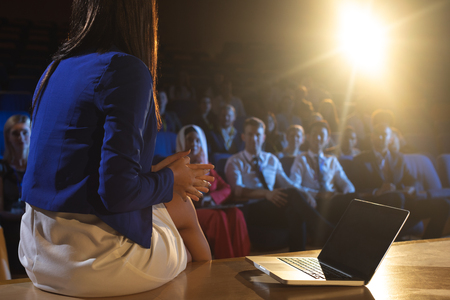 Rear view of beautiful businesswoman sitting with a laptop and discussing with the audience