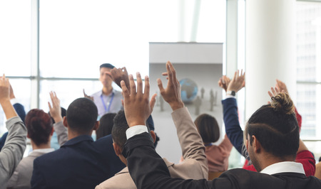 Rear view of diverse business people raising hands while an Asian businessman is speaking at business seminar in office building