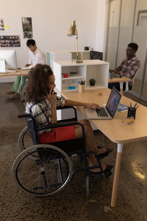 Side view of young disabled mixed-race female executive using laptop while talking on mobile phone at desk in modern office. Stock Photo