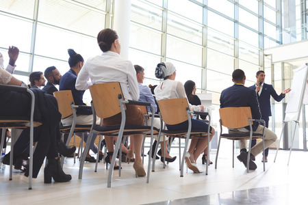 Low angle view of mixed-race businessman showing information on flip chart to group of diverse business people in conference room