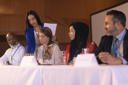 Side view of young mixed race businesswoman showing documents to the panel of speaker Stok Fotoğraf - 122297158