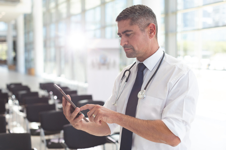 Side view of Caucasian male doctor using digital tablet in a conference room