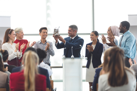 Front view of mixed race businessman holding up award on podium with diverse colleagues standing in front of business professionals at business seminar in office building Stok Fotoğraf - 122297160