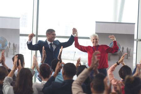 Rear view of diverse business people clapping for multi-ethnic business executive that just finished a successful presentation at business seminar in modern office Stok Fotoğraf