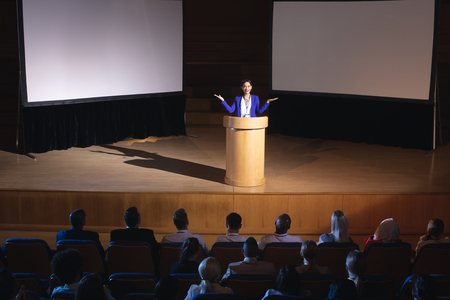 High view of beautiful businesswoman standing around podium and giving presentation to the audience in auditorium Imagens