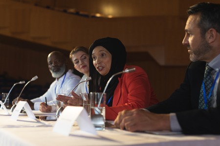 Side view of mixed race businesswoman with executive speaking in speaker while sitting in the auditorium