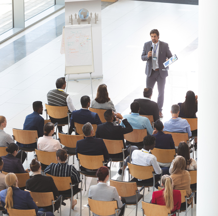 High angle view of Caucasian businessman giving speech at business conference while group of diverse business people listening at conference room.