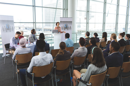 High angle view of mixed-race businesswoman speaking in front of business people sitting at seminar in office building 写真素材