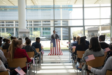 Front view of Caucasian businessman speaking at a business seminar in office building with american flags