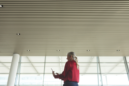 Low angle view of senior Caucasian businesswoman using digital tablet in modern office building Stok Fotoğraf - 122297162