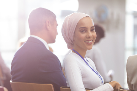 Side view of happy young mixed race businesswoman looking at camera during seminar in office building