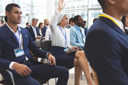 Side view of mixed race businesswoman raising hand in business seminar in office building Stok Fotoğraf - 122297031