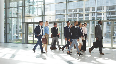 Side view of group of diverse business people walking together in lobby office Stok Fotoğraf - 122297032