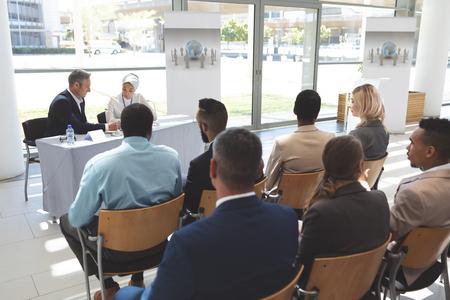 Achteraanzicht van diverse zakenmensen die aan het chatten zijn tijdens een zakelijk seminar in een kantoorgebouw