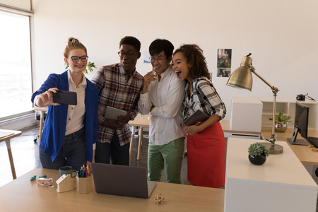 Front view of young diverse business colleagues taking selfie with mobile phone in modern office