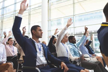Vista lateral de diversos empresarios levantando las manos en seminario de negocios en edificio de oficinas