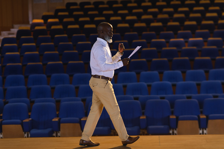Side view of old African-American businessman practicing and learning script while walking in the auditorium