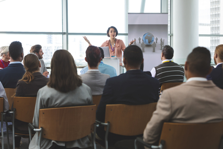 Front view of mixed-race businesswoman speaking animatedly to diverse crowd of business people with laptop in front of her at business seminar in office building