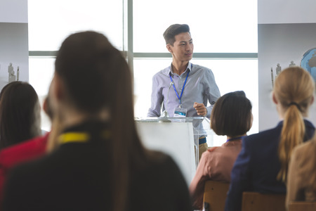 Front view of young Asian businessman speaking at business seminar in front of business people sitting in office building