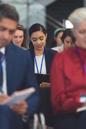 Vorderansicht einer schönen jungen gemischten Geschäftsfrau, die in einem Geschäftsseminar im Bürogebäude auf Notizblock schreibt Standard-Bild