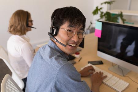 Portrait of happy Asian male executive in headset smiling in modern office. He wears glasses Reklamní fotografie