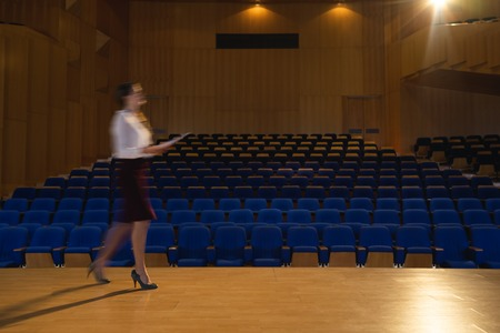 Side view of blur beautiful Caucasian businesswoman practicing and learning script while walking in the auditorium